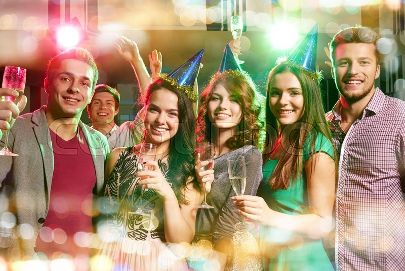 Party, holidays, celebration, nightlife and people concept - smiling friends in party caps with glasses of champagne in club, stock photo
