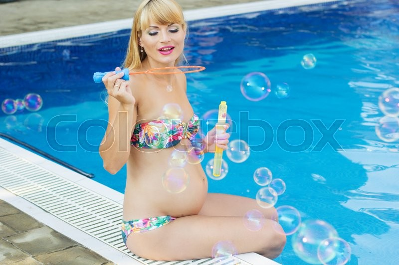Beautiful pregnant blonde woman is stock photo - Where is my nearest swimming pool ...
