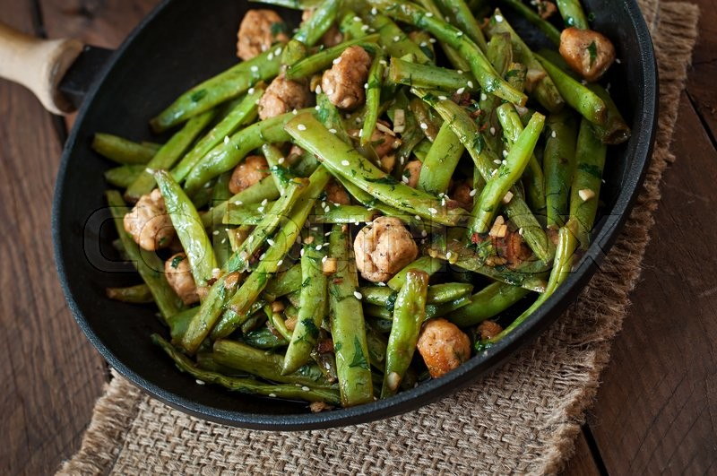 Green beans fried with chicken meatballs and garlic Asian style, stock photo