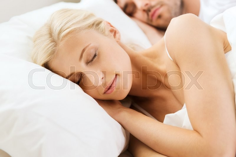 People, rest, relationships and happiness concept - happy woman and man sleeping in bed at home, stock photo