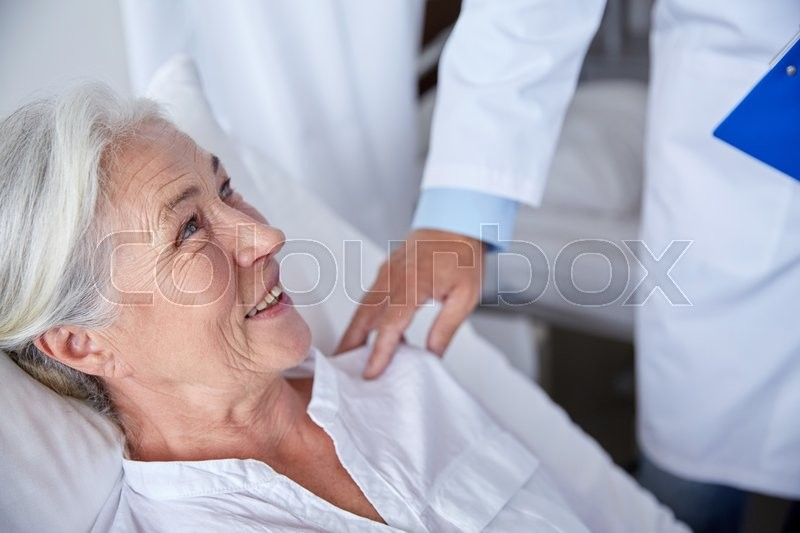 Medicine, age, health care and people concept - doctor visiting happy senior woman at hospital, stock photo