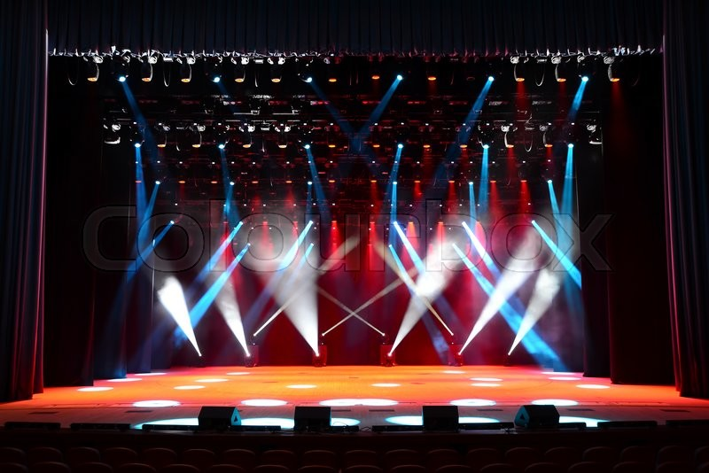 Illuminated empty concert stage with smoke and red, white ...