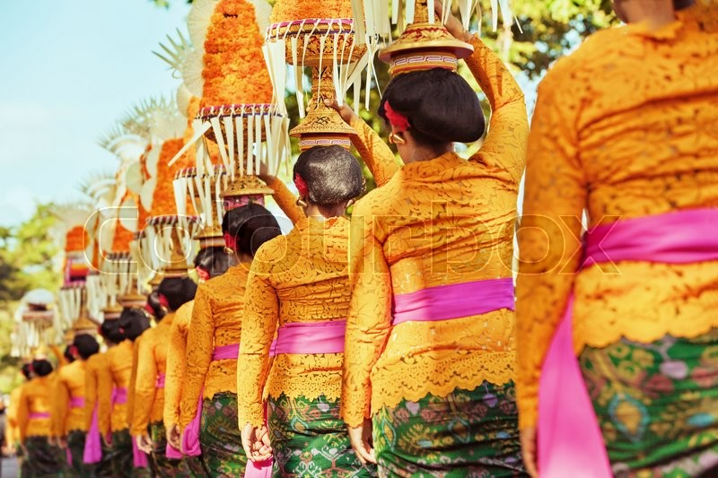 Procession of beautiful Balinese women in traditional costumes  sarong, carry offering on heads