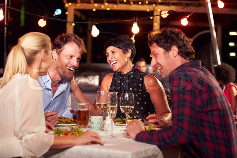 Group of friends eating dinner at rooftop restaurant, stock photo