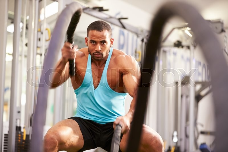 Young man working out with battle ropes at a gym, stock photo