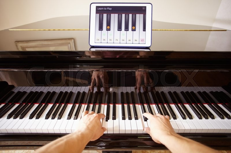 Man Learning To Play Piano Using Digital Tablet Application, stock photo