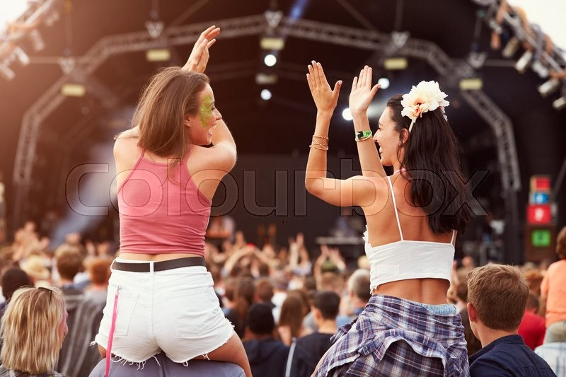 Two girls on shoulders in the crowd at a music festival, stock photo