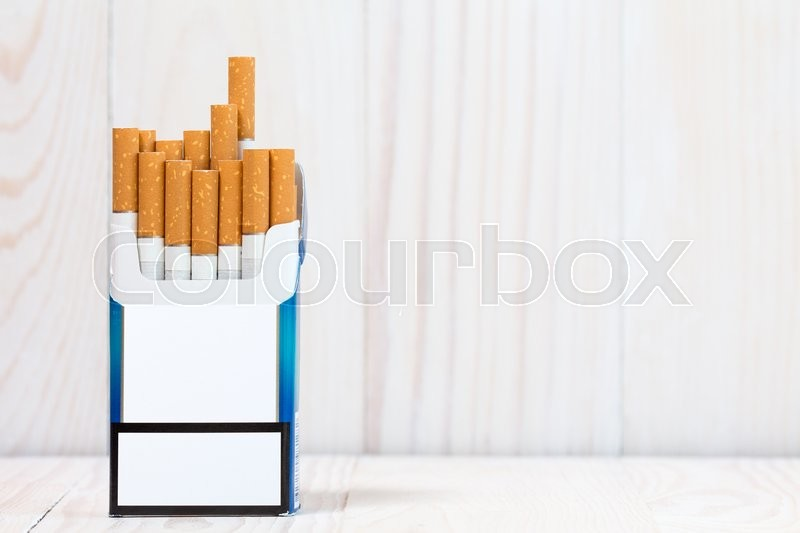Pack of cigarettes on white wood background. With copy-space for text, stock photo