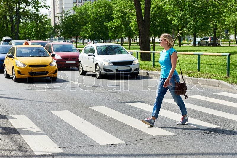 Woman crossing the street at a pedestrian crossing, stock photo