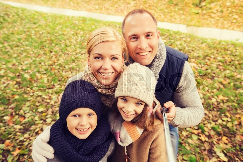 Stock image of 'family, childhood, season, technology and people concept - happy family photographing with selfie stick in autumn park'