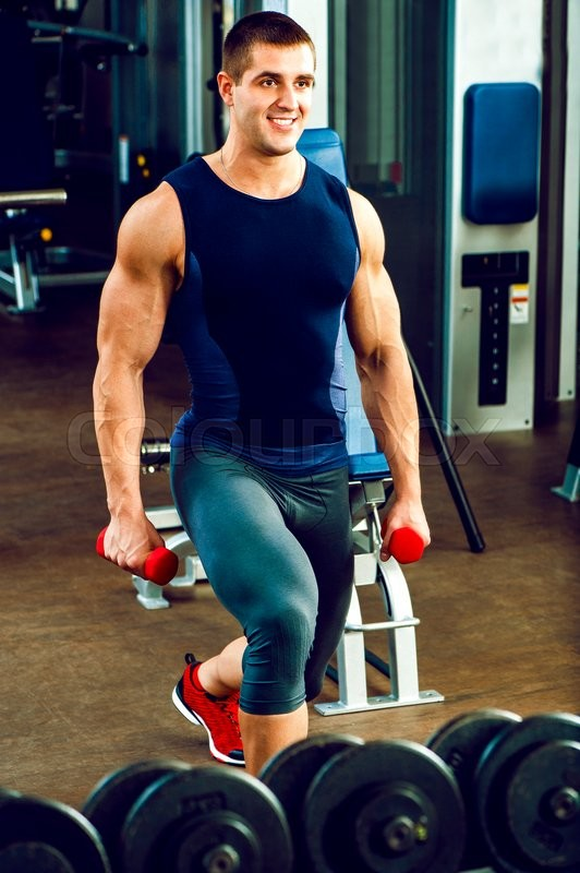 Muscular personal trainer with barbell in sports wear poses in gym.Fashion look.Healthy life.Wellness.Lifestyle.Athletic body.Exercises.Healthcare, stock photo