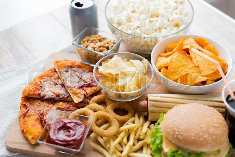 Fast food and unhealthy eating concept - close up of fast food snacks and coca cola drink on wooden table, stock photo