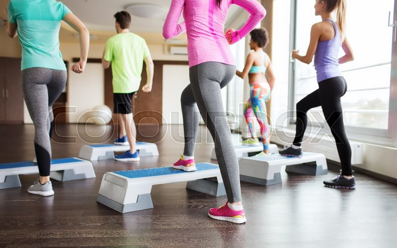 Fitness, sport, training, aerobics and people concept - close up of people working out with steppers in gym from back, stock photo