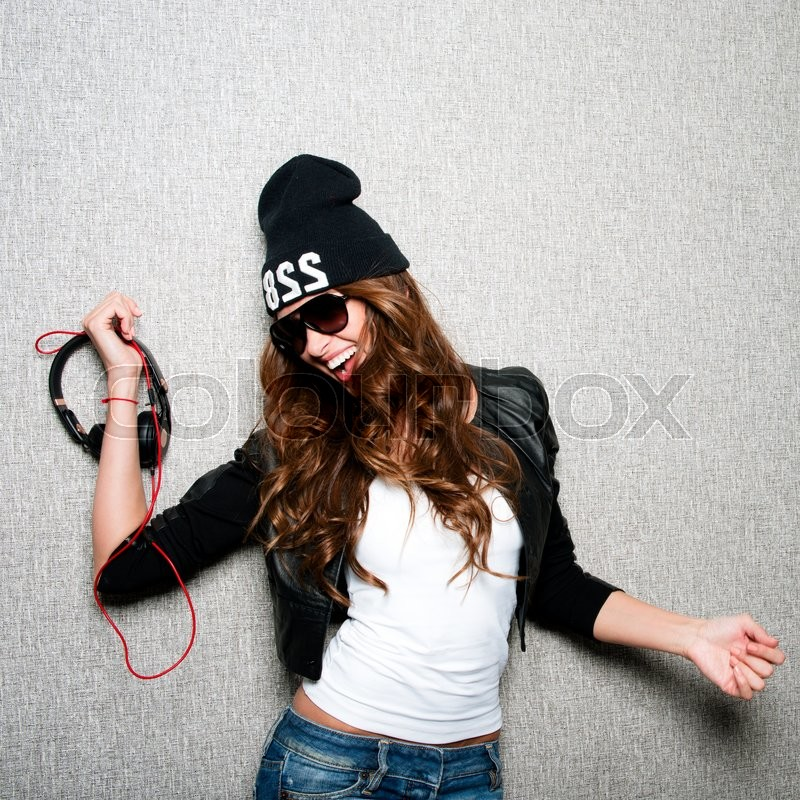 Portrait of beautiful long haired girl with earphones in stylish sunglasses,black cap,white shirt,black jacket and jeans poses on grey background.Fashion look.Stylish image.Casual.Lifestyle.Studio shot.Dj woman, stock photo