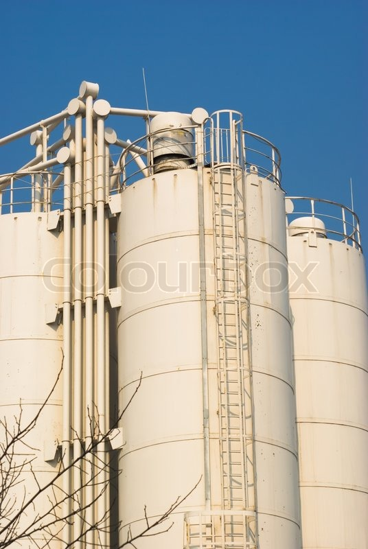 Low-angle shot of ladder and tanks refinery, stock photo