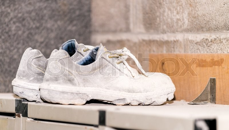 Dirty safety shoes in industrial environment, stock photo