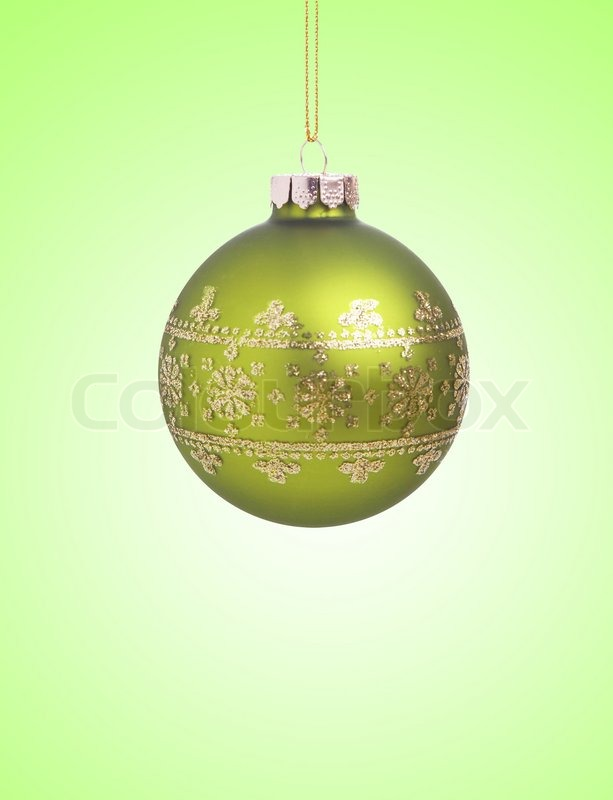Green christmas ball with ribbon on green background with copy space for text, stock photo