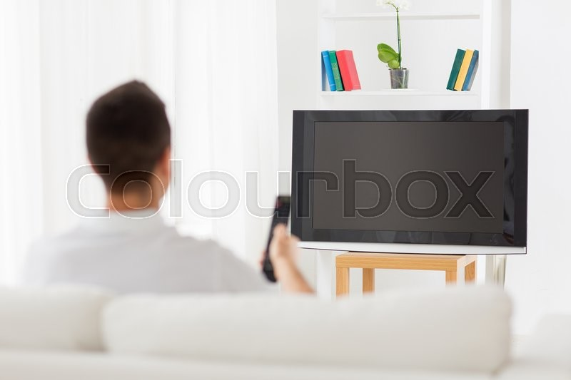 Leisure, technology, mass media and people concept - man watching tv and changing channels at home from back, stock photo