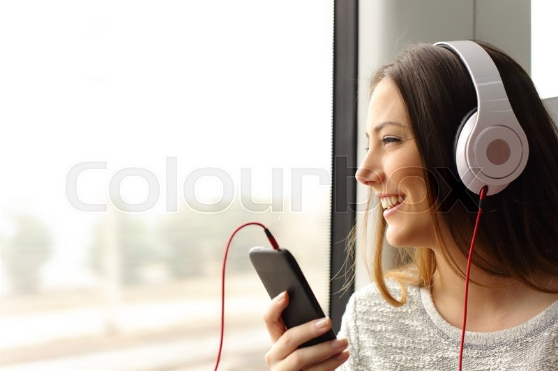 Happy teen passenger listening to the music traveling in a train and looking through the window, stock photo