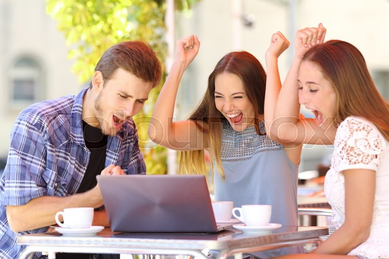 Stock image of happy friends giving a laptop gift to a surprised girl