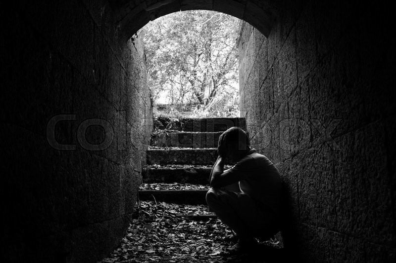 Young sad man sitting inside of dark stone tunnel with stairs in the end, black and white photo, stock photo