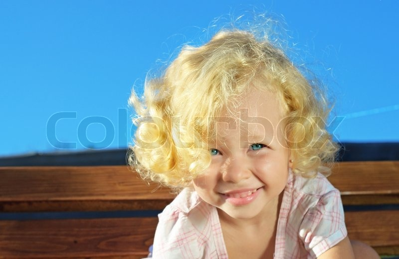 Outdoor shoot of little funny blonde curly girl, stock photo