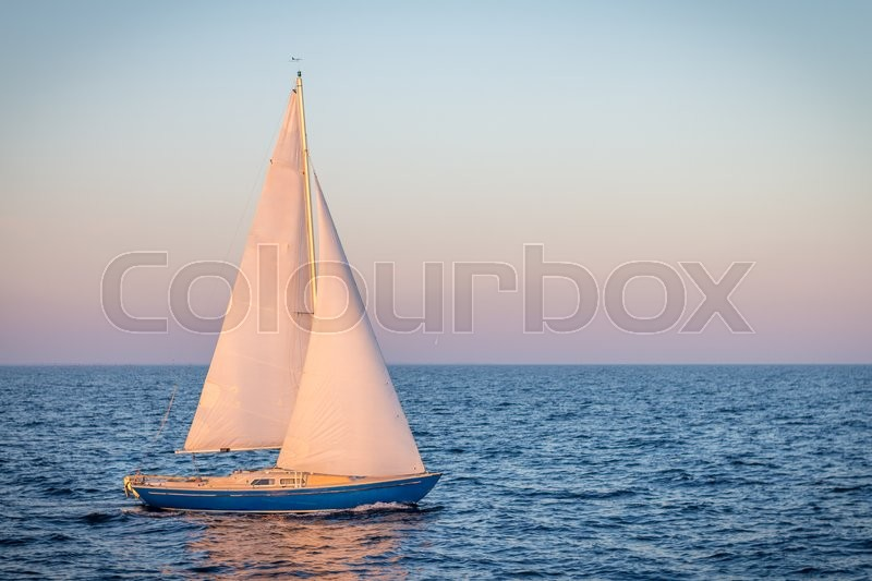 Blue sailboat in the ocean. Can be used for boat, ocean, water, travel, harbor themes, stock photo
