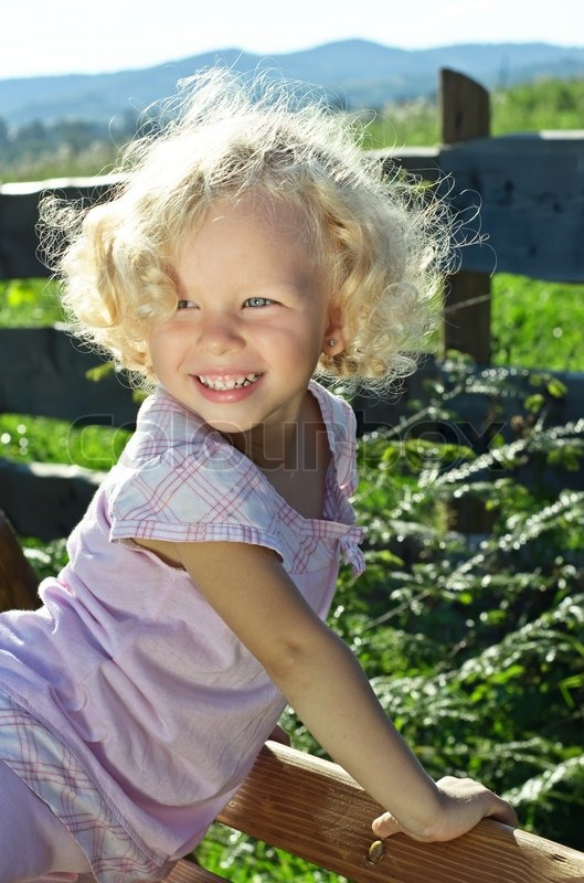 Outdoor Shoot Of Little Funny Blonde Curly Girl Stock