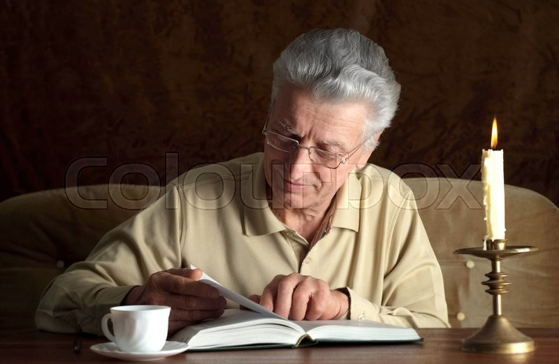 Elderly pensive man writes a letter by candlelight, stock photo