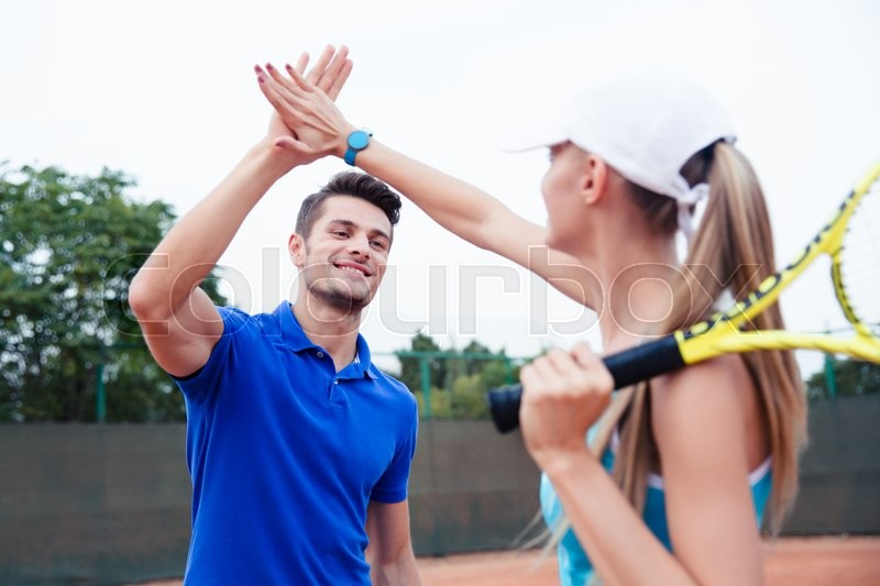 Male and female tennis players gives five at the tennis court after a match, stock photo