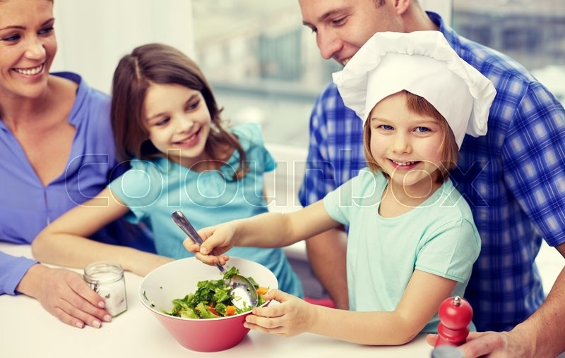 Food, children, culinary and people concept - happy family with two kids cooking vegetables at home, stock photo