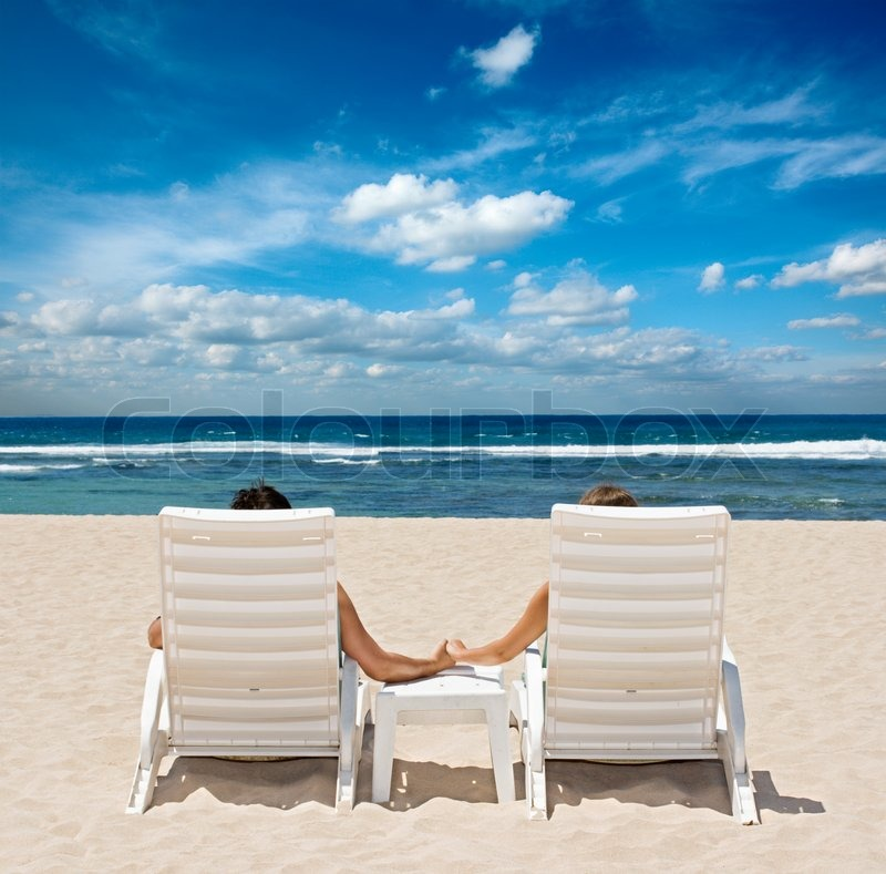 Couple In Beach Chairs Holding Hands Near Ocean Stock