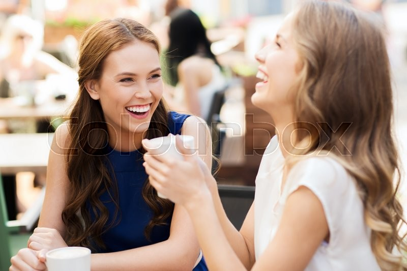 Communication and friendship concept - smiling young women with coffee cups at cafe, stock photo