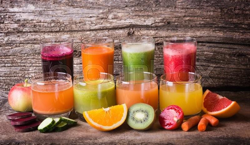 Healthy fruit & vegetable juice on wooden background, stock photo