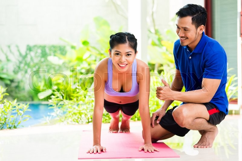 Asian woman and personal trainer at sport exercise doing push-ups, stock photo