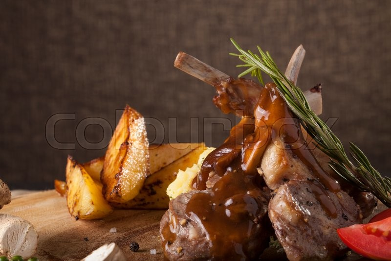 Rack of lamb steak, Rack of lamb steak cut in pieces decorate and seasoning with vegetable and herbs and red wine serve on chopping wood block, stock photo