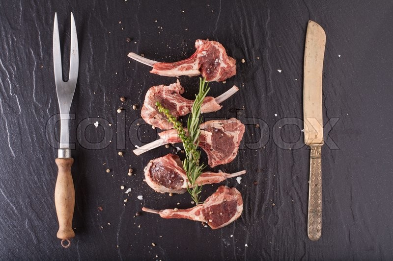 Rack of lamb, Raw rack of lamb cut in pieces decorate and seasoning with rosemary tomato herbs and olive oil fork and knife on black stone, stock photo