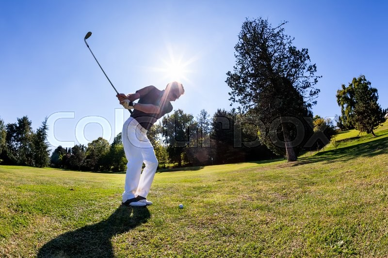Golf sport: male caucasian golfer hits a shoot from the fairway. Summer season, sunny day, stock photo