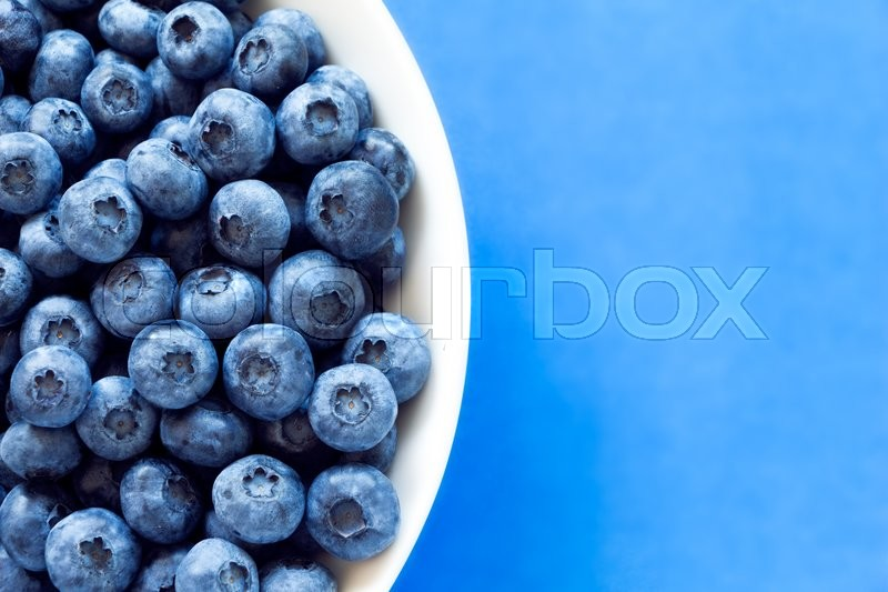 Blueberries in white bowl on colorful blue backround. Can be used for blueberry, blue, color, colorful, vitamin, nutrition, fruit, berries, antioxidant, summer, fun, food themes, stock photo