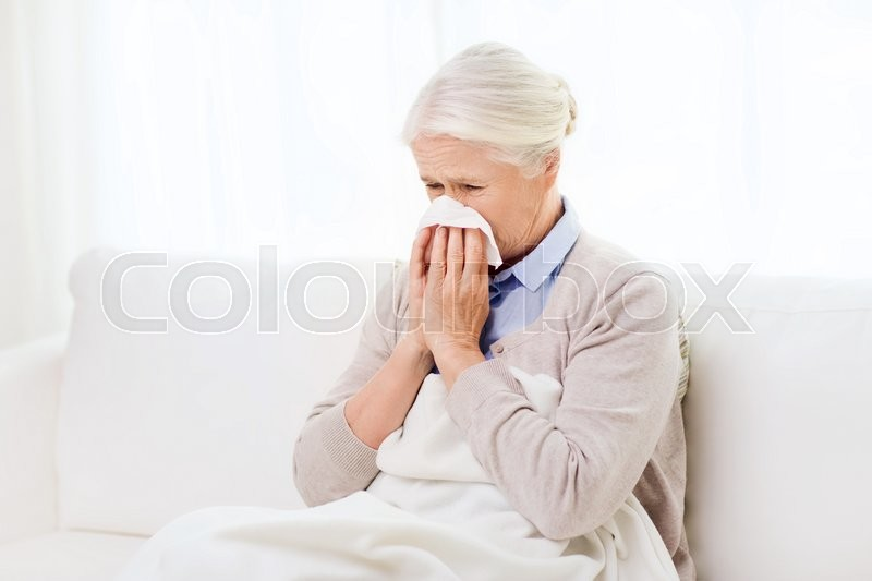 Health care, flu, hygiene, age and people concept - sick senior woman blowing nose to paper napkin at home, stock photo