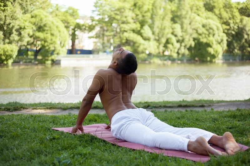 Indian Young Man In White Linen Clothes Practicing Yoga Fitness Pilates On Riverbank Park Lying Bhudjangasana Cobra Pose Full Length