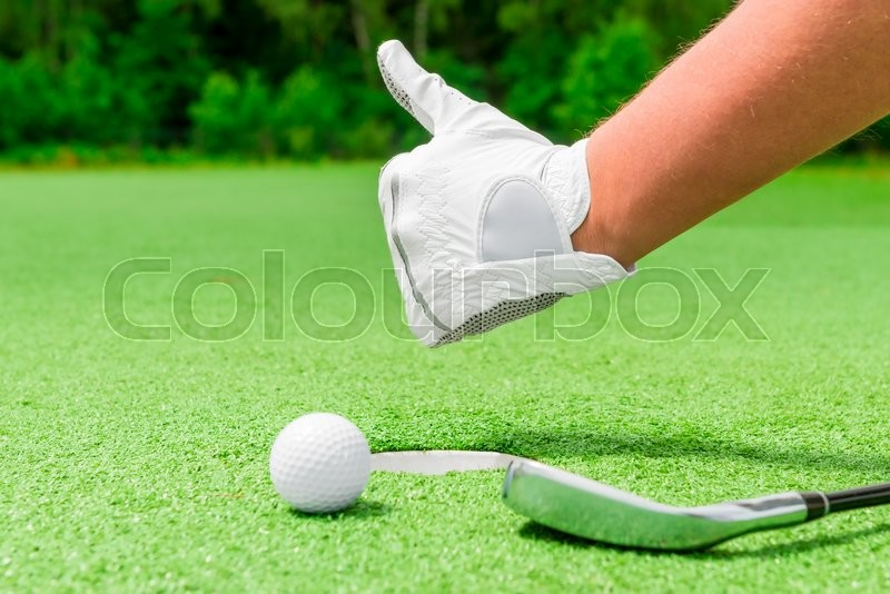 Closeup hand in a white glove and a ball near the hole, stock photo