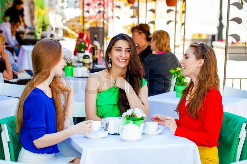 Three happy girlfriends woman sitting at a table in the summer city cafe, stock photo