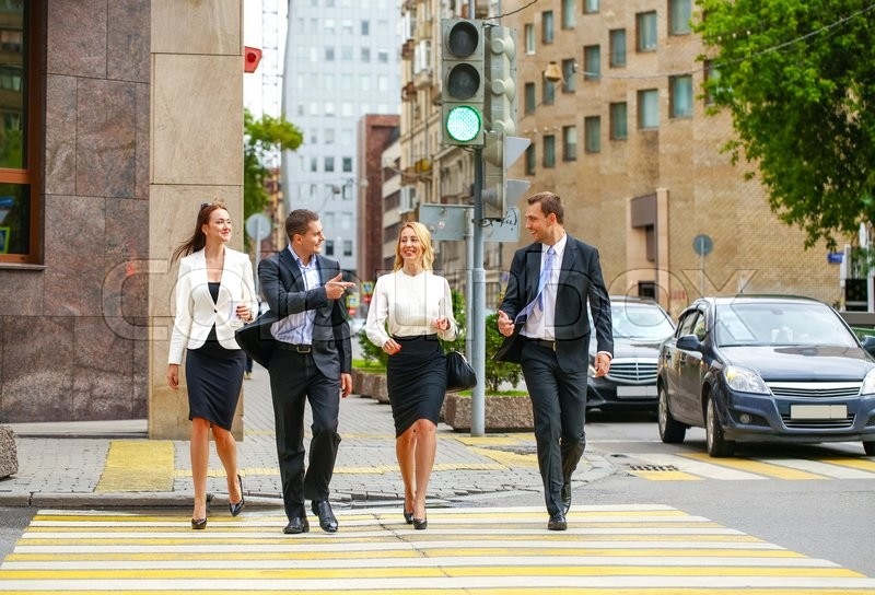 Full length portrait of a young four successful business people crossing the street in the city center, stock photo