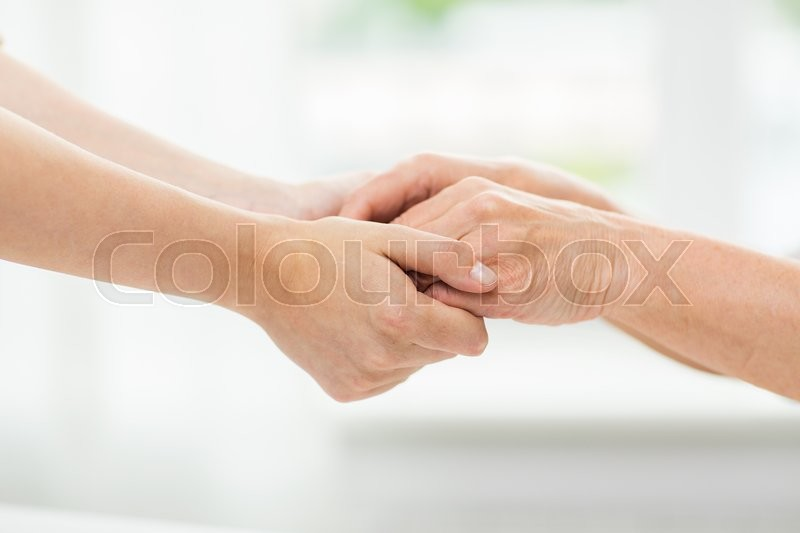 People, age, family, care and support concept - close up of senior woman and young woman holding hands, stock photo