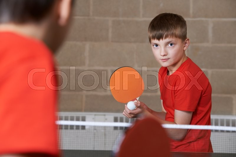 Two Boys Playing Table Tennis Match In School Gym, stock photo
