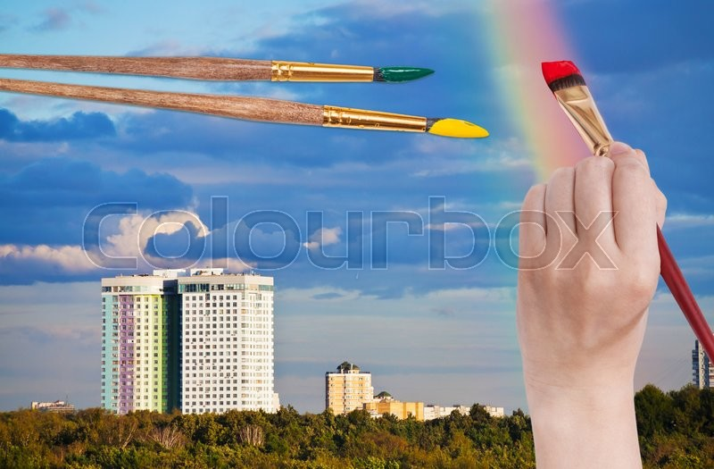Nature concept - hand with paintbrush paints rainbow in blue clouds over urban houses, stock photo