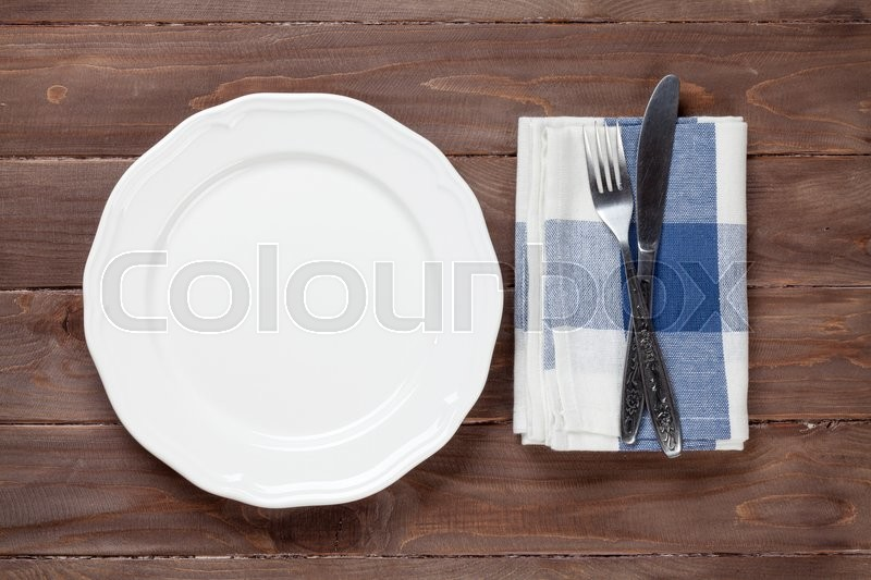 Empty plate and silverware over wooden table background. View from above with copy space, stock photo