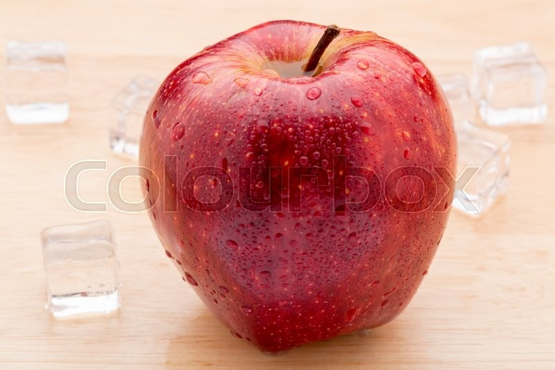 Ripe red apples with water drops on wooden table close up, stock photo