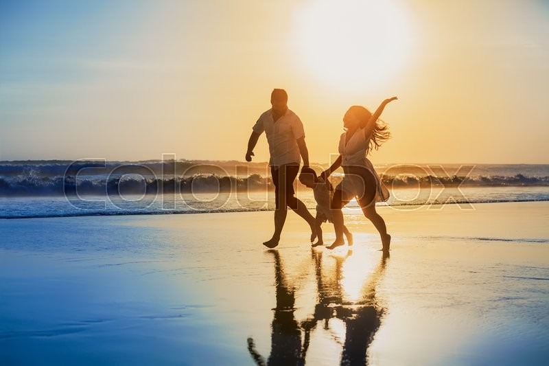Happy family - father, mother, baby son hold hands and run with fun along edge of sunset sea on black sand beach. Active parents and people outdoor activity on tropical summer vacations with children, stock photo